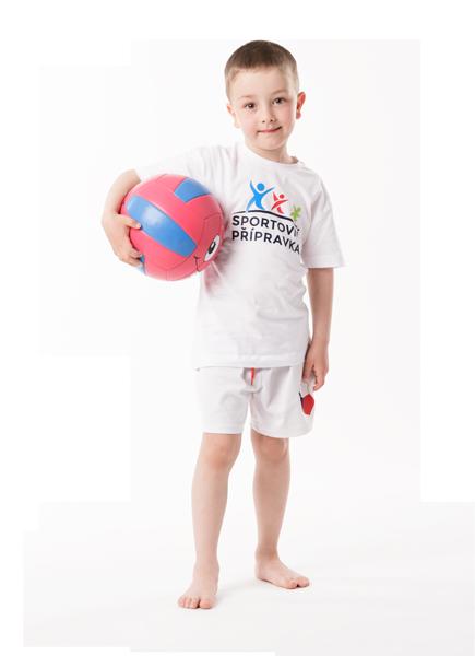 Malý kluk drží míč a má radost ze sportu